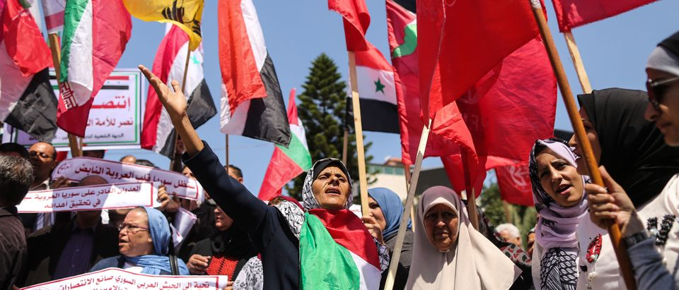 Palestinian protesters chant slogans and wave the flags of Palestine, Syria and Iran during a demonstration against strikes carried out by the United States, Britain and France against Syria's regime, in Gaza City on April 14, 2018, during a demonstration called for by the Popular Front for the Liberation of Palestine (PFLP) and other parties. / AFP PHOTO / MAHMUD HAMS (Photo credit should read MAHMUD HAMS/AFP/Getty Images)