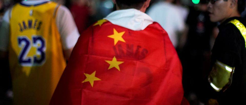 Man wearing a LeBron James jersey wraps himself with a Chinese national flag outside the Mercedes-Benz Arena before the NBA exhibition game between Brooklyn Nets and Los Angeles Lakers in Shanghai