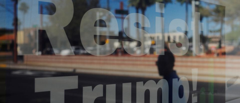 """A pedestrian is reflected in a """"Resist Trump"""" sign in the window of the Arizona Democratic Party office in the Maricopa County city of Phoenix, Arizona, U.S., May 24, 2019. Picture taken May 24, 2019. REUTERS/Brian Snyder"""