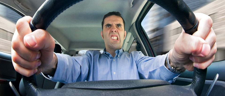 A furious man driving, as seen from behind the wheel. Shot using a very wide fisheye lens.(Shutterstock/JustAnotherPhotographer)