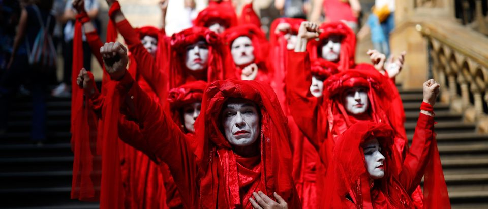 """Extinction Rebellion climate change activists in red costume attend a mass """"die in"""" in the main hall of the Natural History Museum in London on April 22, 2019, on the eighth day of the environmental group's protest calling for political change to combat climate change. - Climate change protesters who have brought parts of London to a standstill said Sunday they were prepared to call a halt if the British government will discuss their demands. Some 963 arrests have been made and 42 people charged in connection with the ongoing Extinction Rebellion protests. (Photo by Tolga Akmen / AFP) (Photo by TOLGA AKMEN/AFP via Getty Images)"""
