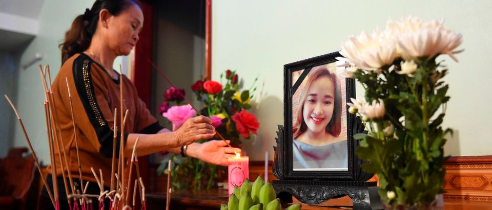 A relative lights an incense stick infront of a portrait of Bui Thi Nhung, who is feared to be among the 39 people found dead in a truck in Britain, inside her house in Vietnam's Nghe An province on Oct. 26, 2019. (Photo by NHAC NGUYEN / AFP via Getty Images)