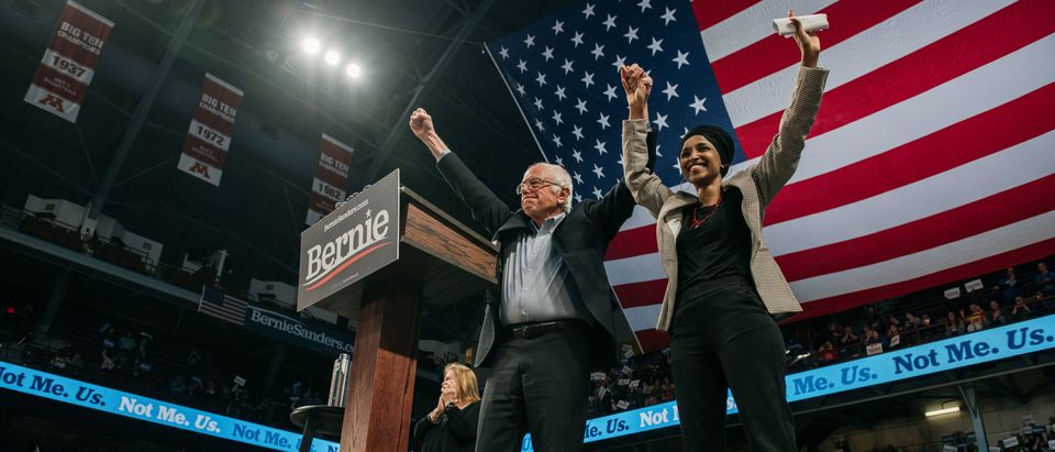 MINNEAPOLIS, MN - NOVEMBER 03: Democratic presidential candidate Sen. Bernie Sanders (I-VT) holdsl hands with Representative Ilhan Omar (D-MN) at a campaign rally at the University of Minnesotas Williams Arena on November, 3, 2019 in Minneapolis, Minnesota. Over 10,000 people, where both Sanders and Omar called for comprehensive immigration reform, welcoming new refugees, and a platform of climate policies known as the Green New Deal (Photo by Scott Heins/Getty Images)