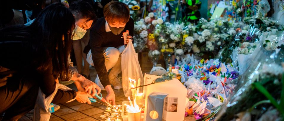 "Mourners pay their respects next to flowers and a banner which reads ""From all of us - God bless Chow Tsz-Lok"" at the site where student Alex Chow, 22, fell during a recent protest in the Tseung Kwan O area on the Kowloon side of Hong Kong on Nov. 8, 2019. ANTHONY WALLACE/AFP via Getty Images"