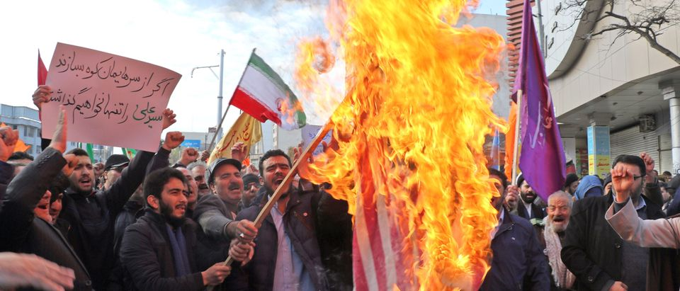 "Iranian men burn a U.S. flag during a protest in support of the Islamic republic's government and supreme leader, Ayatollah Ali Khamenei, in the northwestern city of Ardabil on Nov. 20, 2019, as President Hassan Rouhani said the country's people had defeated an ""enemy conspiracy"" behind a wave of violent street protests. (Photo by STR/AFP via Getty Images)"