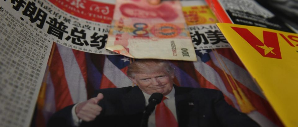 A vendor picks up a 100 yuan note above a newspaper featuring a photo of U.S. President-elect Donald Trump, at a news stand in Beijing on Nov. 10, 2016. GREG BAKER/AFP via Getty Images