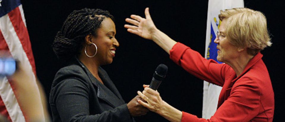 Massachusetts Democratic congressional candidate Ayanna Pressley (L) greets US Senator Elizabeth Warren (D-MA) during a town hall meeting in Roxbury, Massachusetts, October 13, 2018
