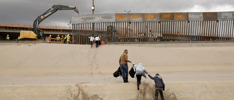 Migrants cross a river next to an excavator working in a section of the new wall between El Paso and Ciudad Juarez