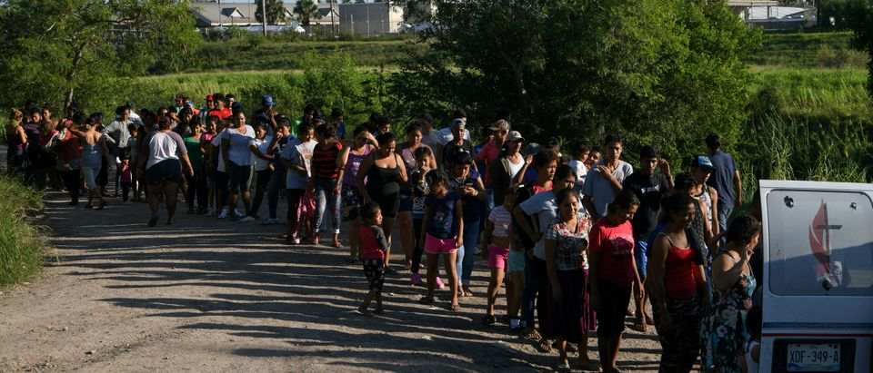 "Migrants, most of them asylum seekers sent back to Mexico from the U.S. under the ""Remain in Mexico"" program officially named Migrant Protection Protocols (MPP), wait in line to receive bottles of drinking water by a makeshift encampment in Matamoros, Tamaulipas, Mexico, Oct. 28, 2019. REUTERS/Loren Elliott"