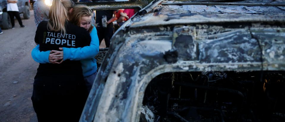Relatives of slain members of Mexican-American families belonging to Mormon communities react next to the burnt wreckage of a vehicle where some of their relatives died, in Bavispe, Sonora state, Mexico, Nov. 5, 2019. REUTERS/Jose Luis Gonzalez