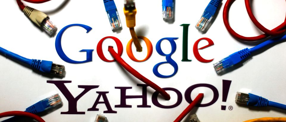 An illustration picture shows the logos of Google and Yahoo connected with LAN cables in a Berlin office Oct. 31, 2013. REUTERS/Pawel Kopczynski