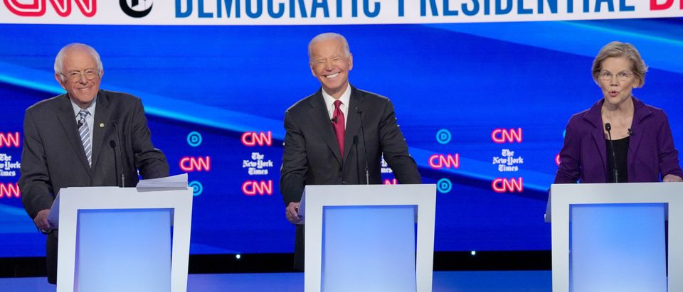 FILE PHOTO: Democratic presidential candidates Senator Bernie Sanders and former Vice President Joe Biden listen to Senator Elizabeth Warren as they debate during the fourth U.S. Democratic presidential candidates 2020 election debate in Westerville, Ohio