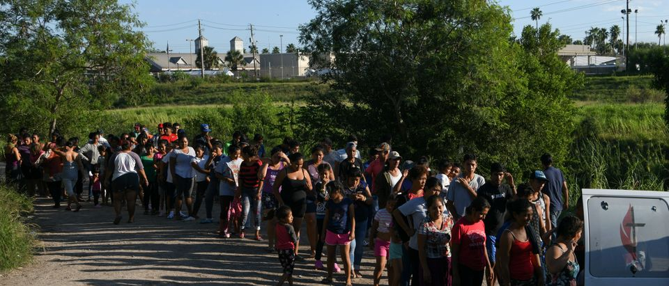 """Migrants, most of them asylum seekers sent back to Mexico from the U.S. under the """"Remain in Mexico"""" program officially named Migrant Protection Protocols (MPP), wait in line to receive bottles of drinking water by a makeshift encampment in Matamoros, Tamaulipas, Mexico, Oct. 28, 2019. REUTERS/Loren Elliott"""