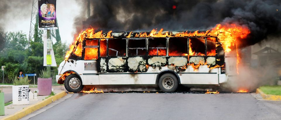 "A burning bus, set alight by cartel gunmen to block a road, is pictured during clashes with federal forces following the detention of Ovidio Guzman, son of drug kingpin Joaquin ""El Chapo"" Guzman, in Culiacan, Sinaloa state, Mexico, Oct. 17, 2019. REUTERS/Stringer"