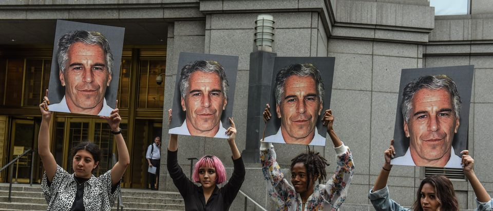 """A protest group called """"Hot Mess"""" hold up signs of Jeffrey Epstein in front of the Federal courthouse on July 8, 2019 in New York City. (Stephanie Keith/Getty Images)"""