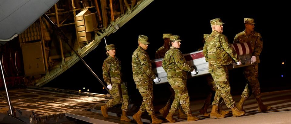 Military personnel carry a transfer case for fallen service member, U.S. Navy Ensign Joshua Watson, during a dignified transfer at Dover Air Force Base on December 8, 2019 in Dover, Delaware. (Mark Makela/Getty Images)