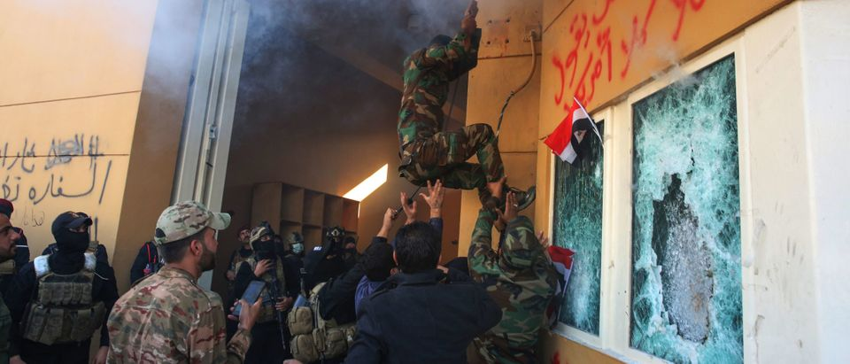 Members of Iraq's Hashed al-Shaabi military network attempt to break into the US embassy in the capital Baghdad, on December 31, 2019, during a rally to vent anger over weekend air strikes that killed pro-Iran fighters in western Iraq. (AHMAD AL-RUBAYE/AFP via Getty Images)