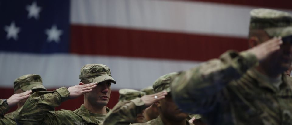 Soldiers from the U.S. Army's 3rd Brigade Combat Team, 1st Infantry Division, salute during the playing of the Star Spangled Banner during a homecoming ceremony in the Natcher Physical Fitness Center on Fort Knox on Feb. 27, 2014 in Fort Knox, Kentucky. (Photo by Luke Sharrett/Getty Images)