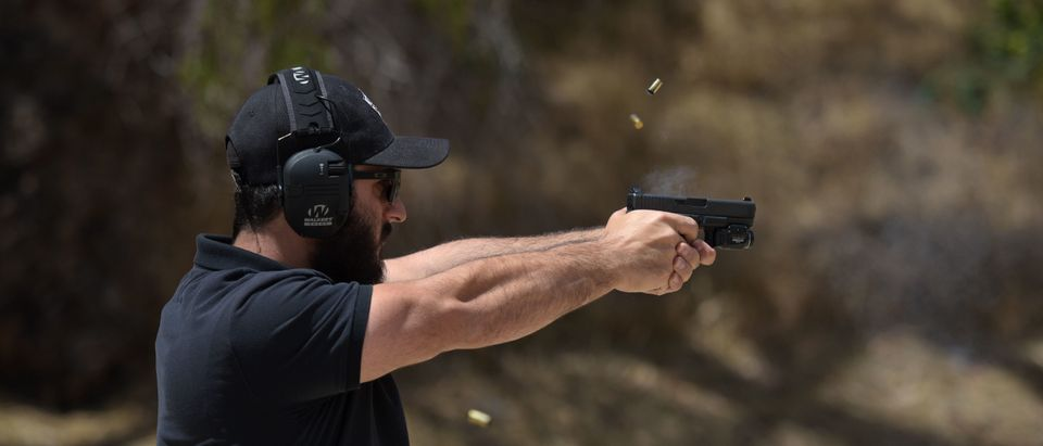 """Rabbi Raziel Cohen, aka """"Tactical Rabbi,"""" shoots a Glock 9mm pistol during a demonstration on May 20, 2019 in Pacoima, California. (Agustin Paullier/AFP/Getty Images)"""