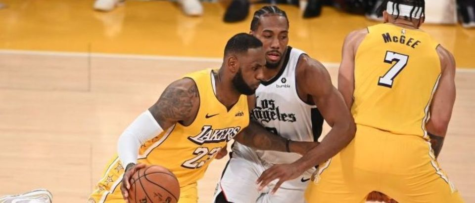 Los Angeles Lakers forward LeBron James (L) drives past Los Angeles Clippers forward Kawhi Leonard (C) on a pick by Lakers center JaVale McGee (R) during a Christmas Day National Basketball Association (NBA) match-up between the Los Angeles Clippers and Los Angeles Lakers at the Staples Center in Los Angeles, California on December 25, 2019. (Photo by ROBYN BECK/AFP via Getty Images)