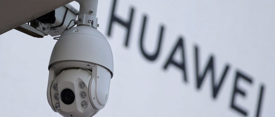 A surveillance camera is seen next to a sign of Huawei in Beijing