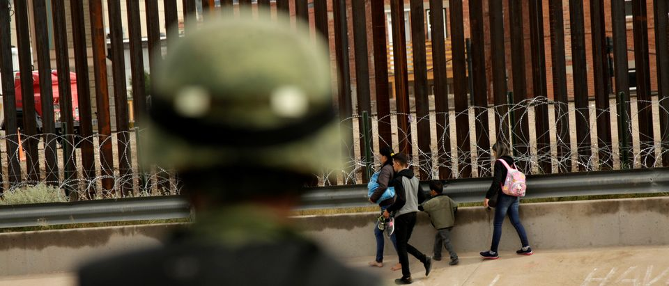 A National Guard soldier observes migrants after crossing illegally into El Paso, Texas, U.S. to turn themselves in to U.S. Border Patrol agents to ask for asylum, as seen from Ciudad Juarez, Mexico, Sept. 15, 2019. REUTERS/Jose Luis Gonzalez