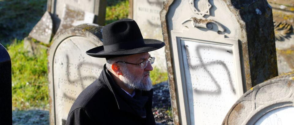 A man walks past graves desecrated with swastikas at the Jewish cemetery in Westhoffen, near Strasbourg, France, December 4, 2019. REUTERS/Arnd Wiegmann)