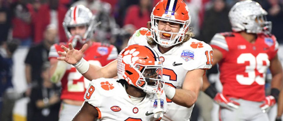 GLENDALE, ARIZONA - DECEMBER 28: Travis Etienne #9 is congratulated by his teammate Trevor Lawrence #16 of the Clemson Tigers after his 8-yard touchdown run against the Ohio State Buckeyes in the first half during the College Football Playoff Semifinal at the PlayStation Fiesta Bowl at State Farm Stadium on December 28, 2019 in Glendale, Arizona. (Photo by Norm Hall/Getty Images)