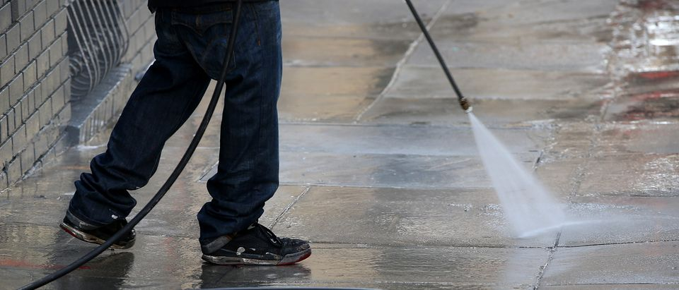 A worker uses a power washer to clean the sidewalk in front of a building on May 6, 2015 in San Francisco, California. (Photo by Justin Sullivan/Getty Images)