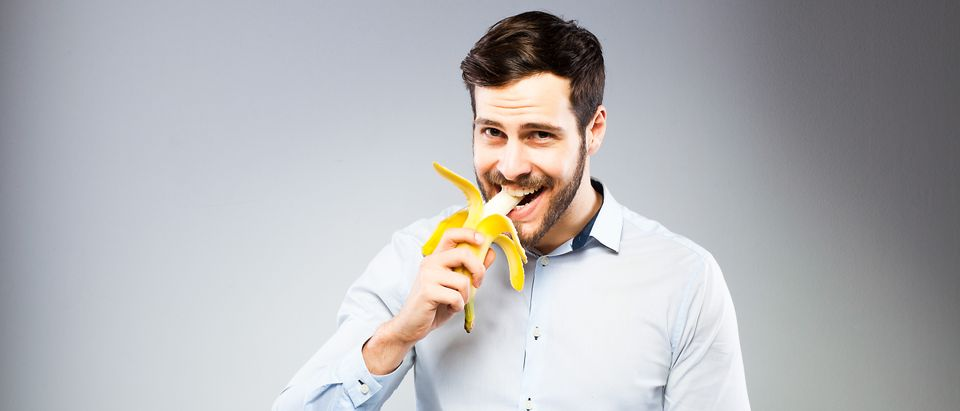 Man eating banana. (Shutterstock/All kind of people)