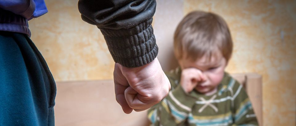 Scared or terrified child boy sitting at wall with the fist. Aggressive parent and frightened child in corner. Domestic Family violence and aggression concept violence