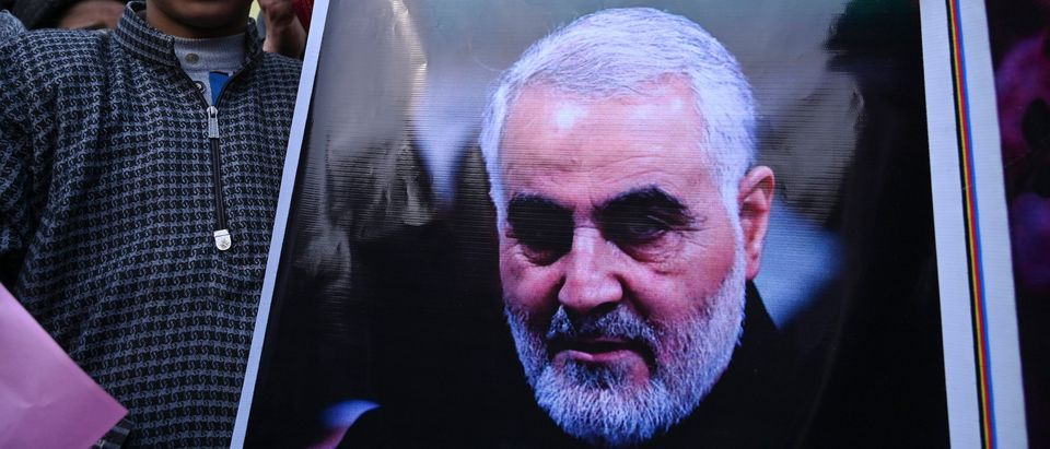 "A protester holds a poster with the image of top Iranian commander Qasem Soleimani, who was killed in a US airstrike in Iraq, in the Kashmiri town of Magam on January 3, 2020. - Hundreds of people in Indian Kashmir staged ""anti-American"" demonstrations in the troubled territory on January 3 within hours of US forces killing a top Iranian commander. (Photo by TAUSEEF MUSTAFA/AFP via Getty Images)"