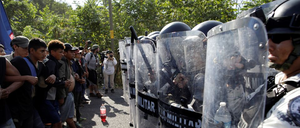 Security forces holding riot shields block a caravan of mostly Central American migrants, near Frontera Hidalgo, Chiapas