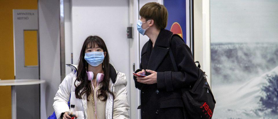 Air travelers wear masks as they arrive at Ivalo Airport, Finland Jan. 24, 2020. Lehtikuva/Tarmo Lehtosalo via REUTERS