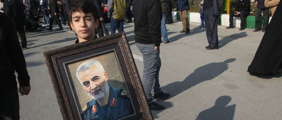 A boy holds a portrait of Iranian Revolutionary Guards Major General Qasem Soleimani during a demonstration in Tehran on January 3, 2020 against the killing of the top commander in a US strike in Baghdad. (ATTA KENARE/AFP via Getty Images)