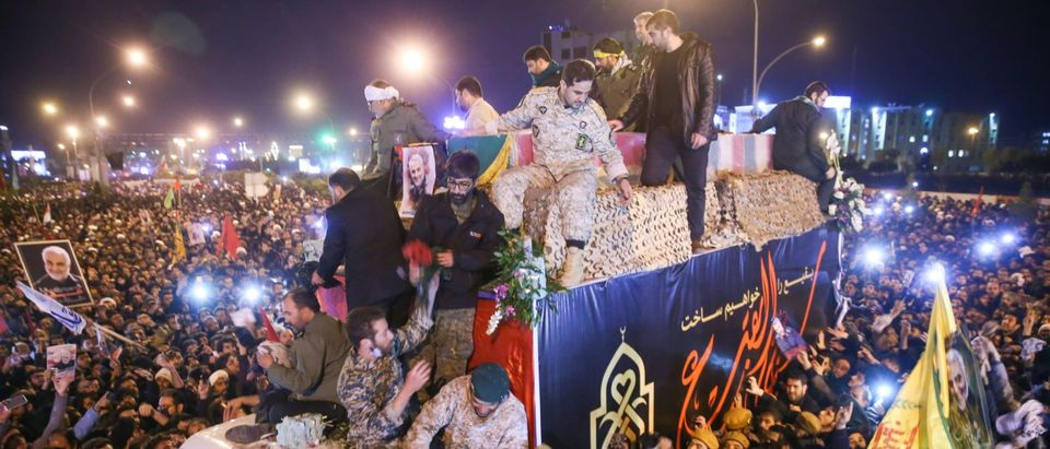 Iranians gather around a vehicle carrying the caskets of slain military commander Qasem Soleimani and others during a funeral procession after the bodies arrived in the northeastern city of Qom on January 6, 2020 following a cermony in the capital Tehran. (Photo by Medhi MARIZAD / FARS NEWS / AFP / GETTY IMAGES)