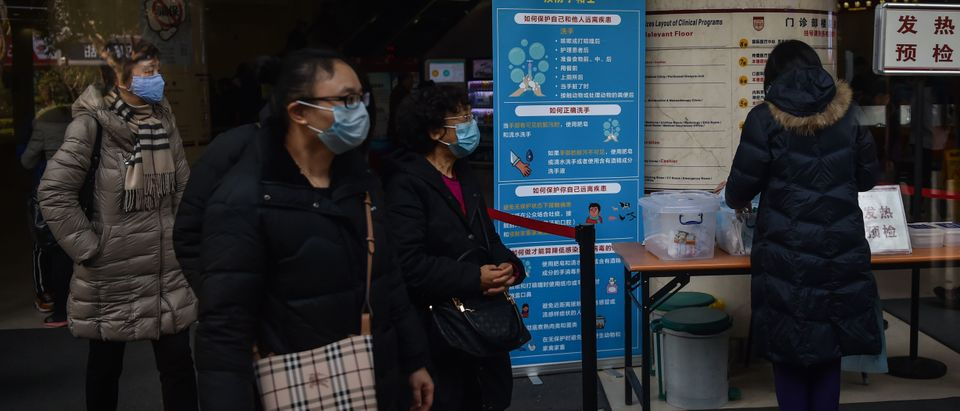 People walk next to signage detailing hygenic practices to prevent the spread of a SARS-like coronavirus at the Huashan Hospital in Shanghai on January 21, 2020. - China has confirmed human-to-human transmission in the outbreak of a new SARS-like virus as the number of cases soared and the World Health Organization said it would consider declaring an international public health emergency.(Photo by HECTOR RETAMAL/AFP via Getty Images)