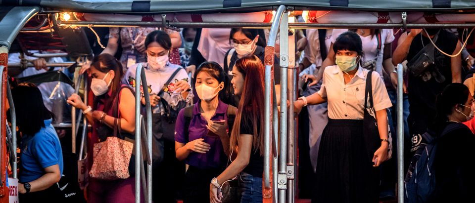 Commuters with protective facemasks board a canal boat at Pratunam Pier in Bangkok on January 30, 2020. - A Thai surgical mask factory, producing 10 million masks a month, increased working hours to cope with the rising demand following an outbreak of SARS-like virus in China, with their product exported mostly to US and Europe the rest sold on the domestic market. (Photo by Mladen ANTONOV / AFP) (Photo by MLADEN ANTONOV/AFP via Getty Images)