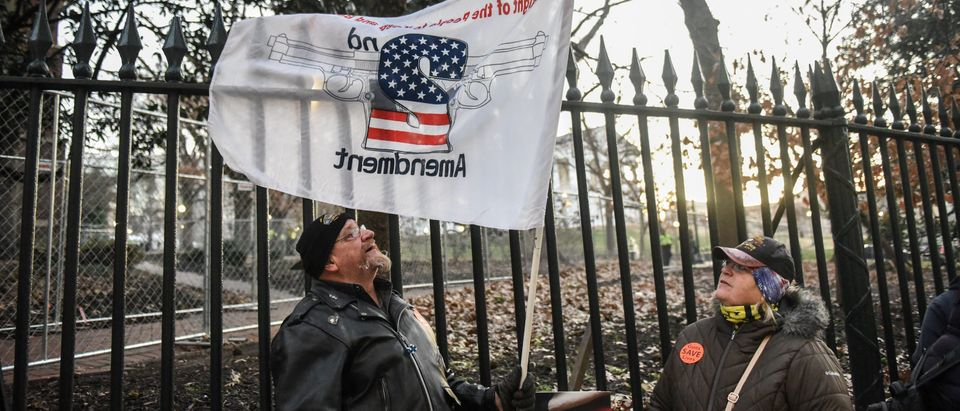 People hold a flag that advocates for the second amendment in front of the Virginia State Capitol building in Richmond, Virginia, U.S. January 20, 2020. (REUTERS/Stephanie Keith)