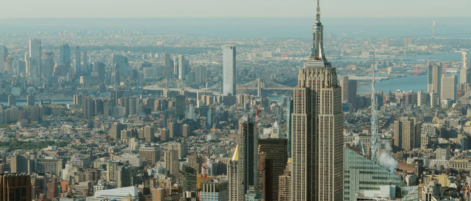 The Empire State Building rises above Manhattan in front of the Brooklyn and Manhattan bridges as seen from an apartment in the Central Park Tower building as the building celebrates its topping out in New York