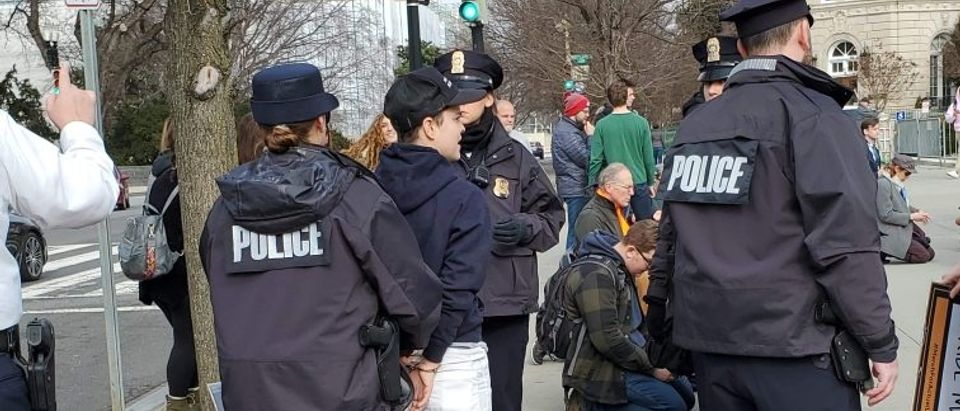 The protester is handcuffed. Photo courtesy of Selene Cerankosky