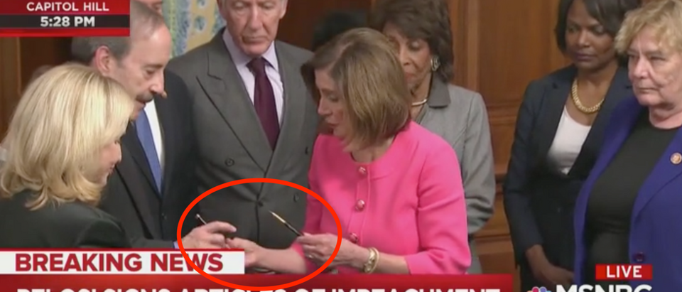 House Speaker Nancy Pelosi hands out souvenir impeachment pens. Screen Shot/MSNBC