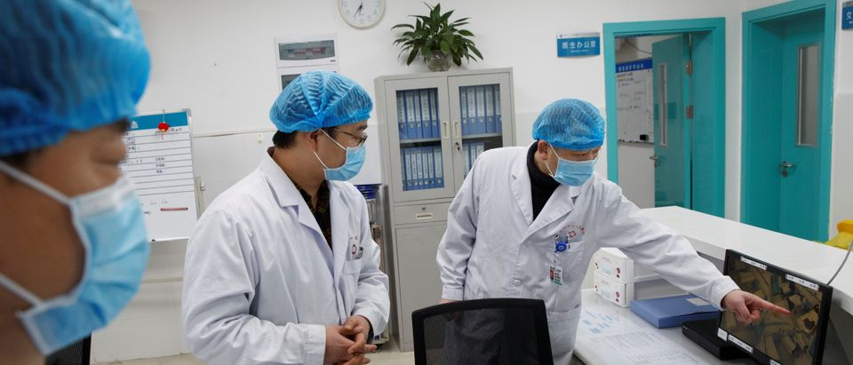 Doctors look at a screen that shows the ward where patients who are infected with the coronavirus are treated at the First People's Hospital in Yueyang