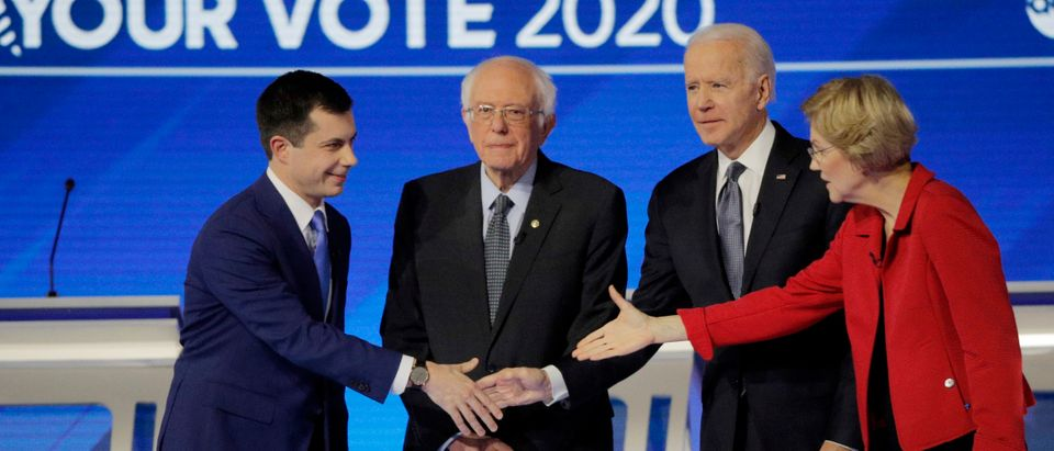 Democratic 2020 U.S. presidential candidates former South Bend Mayor Pete Buttigieg, Senator Bernie Sanders, former Vice President Joe Biden and Senator Elizabeth Warren gather onstage before the start of the eighth Democratic 2020 presidential debate at Saint Anselm College in Manchester, New Hampshire, U.S., February 7, 2020. REUTERS/Brendan McDermid