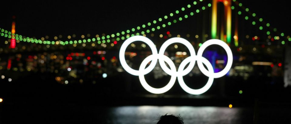 A member of the public looks on as the Olympic rings are illuminated for the first time to mark 6 months to go to the Olympic games at Odaiba Marine Park on Jan. 24, 2020 in Tokyo, Japan. (Clive Rose/Getty Images)