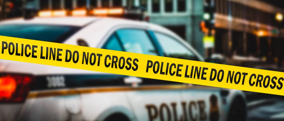 American police tape hangs near a police car. (Joerg Huettenhoelscher/Shutterstock)