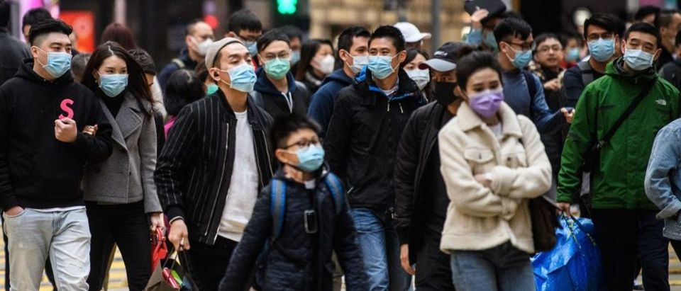 TOPSHOT - Pedestrians wearing face masks cross a road during a Lunar New Year of the Rat public holiday in Hong Kong on January 27, 2020, as a preventative measure following a coronavirus outbreak which began in the Chinese city of Wuhan. (Photo by ANTHONY WALLACE/AFP via Getty Images)