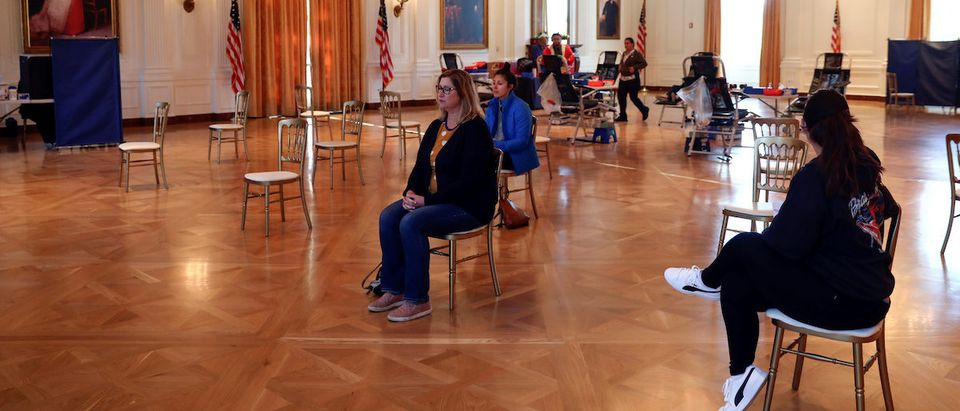 People sit in chairs six feet apart for social distancing while waiting to give blood at a donation center inside the White House East Room replica at the Richard Nixon Presidential Library and Museum to help with a shortage of blood donations due to the coronavirus disease (COVID-19) outbreak, in Yorba Linda, California, U.S., March 30, 2020. REUTERS/Patrick T. Fallon