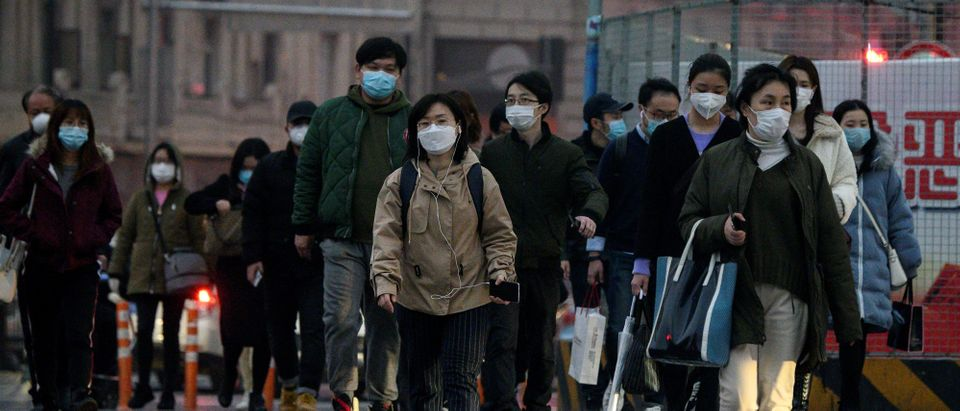 People wearing protective facemasks cross a street in Shanghai on February 25, 2020. (NOEL CELIS/AFP via Getty Images)
