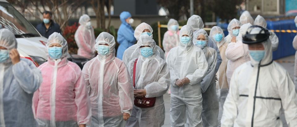 Patients who recovered from the COVID-19 coronavirus wear protective clothing as they line up to be tested again at a hospital in Wuhan, in China's central Hubei province on March 14, 2020. (STR/AFP via Getty Images)